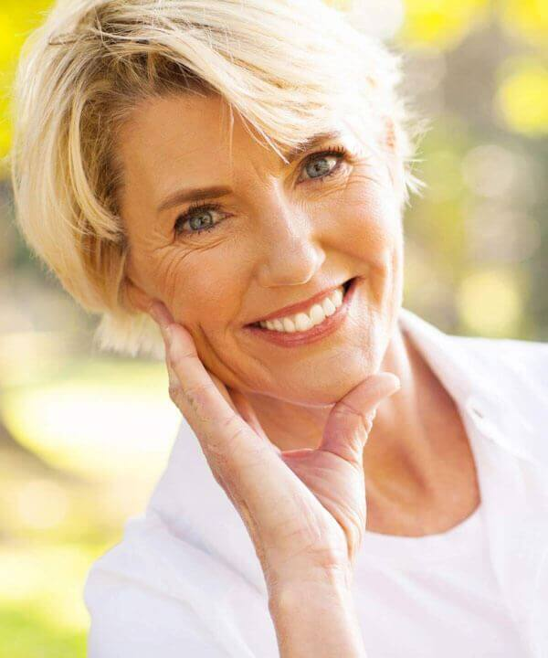 elderly woman with dental implants smiling in park
