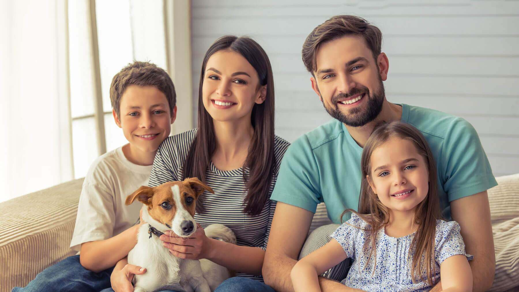 family with beautiful smiles and terrier